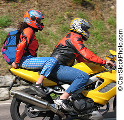 Risk - Two young people on a motorcycle. Clothing is fairly...