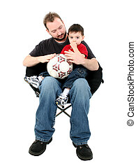 Father Son Ball - Father and son in chair holding ball over...