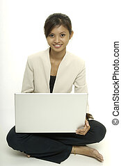 With Laptop - A pretty young asian woman sits on the floor...