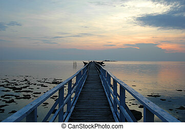 Jetty at Sunrise - A wooden jetty on an Indonesian island at...