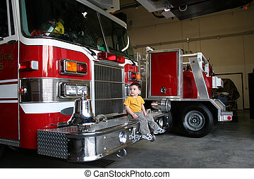 Boy Child Firetruck - Toddler boy sitting on and looking at...