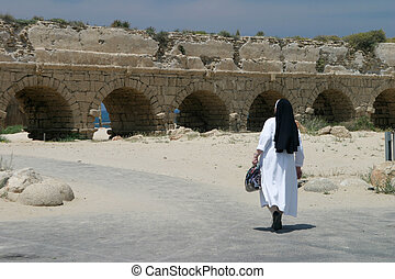 Visit the holy land - A nun at the aqueduct, Caesarea,...