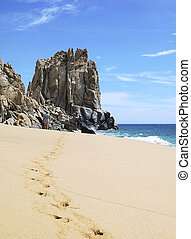 Mexico Beach Walk - A man walks toward Finisterra Rock,...