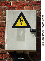 Fuse box with black/yellow sign warning for risk of...