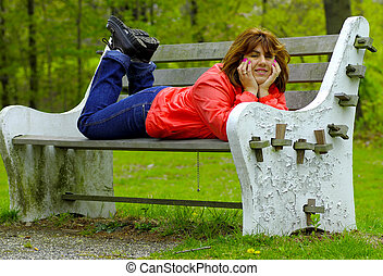 Woman on a Bench - Woman Laying Down on a Park Bench.