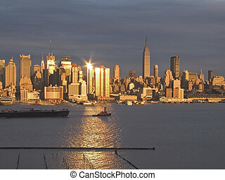 Sunset Skyline - A tugboat pulls a barge along the Hudson...