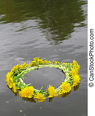 Wreath from dandelions floats in the river