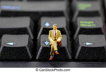 Business Man - Miniature Business Man Sitting on a Keyboard....