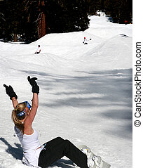 Fun snowboarding - Blond woman cheering two snowboarders