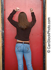 Locked Out - Young woman knocking on red door trying to get...