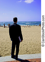 Holiday Hope - Businessman on the beach wishing he wasnt