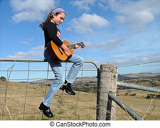 Sitting on a fence - girl playing guitar sitting on fence