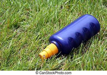 Sunscreen - A bottle of sunscreen in the grass