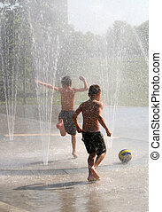 Boys in Fountain - Two boys playing in a fountain in the...