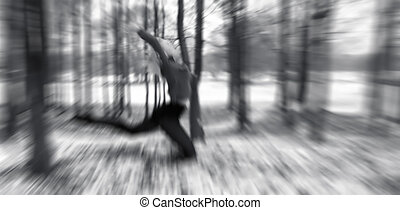 Wood nymph - Monochrome blur of dancer leaping in woods, in...