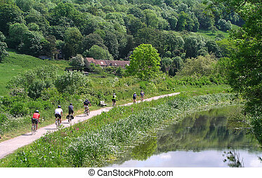 Cycling - Group of cyclists riding along side the canal