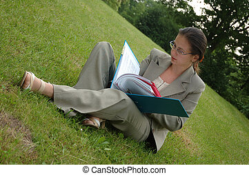 she works everywhere - young woman sits on the grass in park...