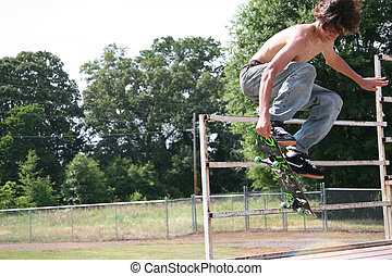 Skateboarder in the air - Teen skateboarder flying through...