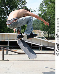 Teen Boy Skateboarding Outdoors - Teen boy shirtless in...