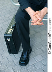 Business briefcase - Business man sitting next to his...