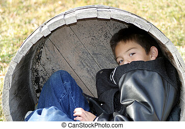 Young Boy Playing - A young boy playing inside a wood barrel...