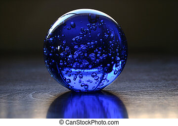Glass Ball - One blue colored glass ball on a wooden table...