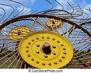 Mechanical Sunflower - A close up view of a yellow hay rake...