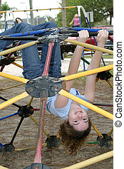 Jungle Gym Girl 2 - A young girl hanging upside down from a...