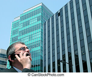 Businessman - a businessman speaking to the phone in a big...