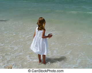 Little Beachcomber 2 - A little girl, holding a seashell and...