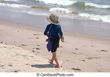 walking boy - a young boy walking at the beach