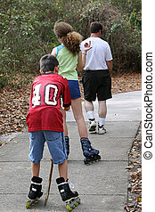 Skating Away - Two teens skating along a sidewalk with an...