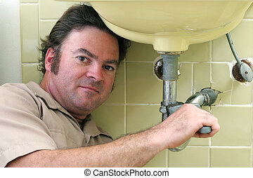 Plumber Under Sink - A plumber working on a pipe under a...