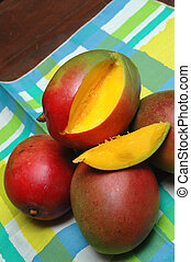 mangoes on a table cloth with one sliced open