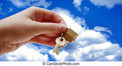Security - Hand holding lock and keys - sky background