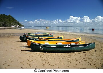 Canoes on Beach - Colourful canoes on sandy beach with water...
