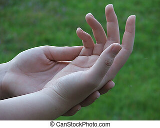 Kindness - Young womans softly posed hands in shallow DOF