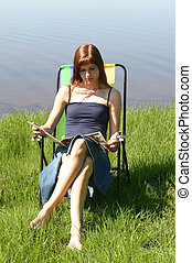 Reading by the sea - Girl sitting in a sun chair reading a...