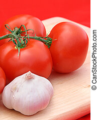 Tomato and Garlic RED - Tomatoes garlic on a wooden cutting...