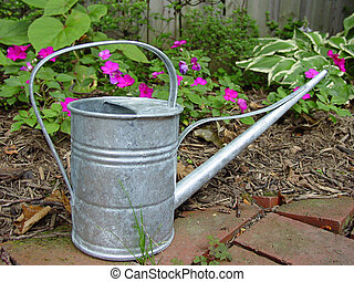 Watering Can - An old fashioned watering can in front of a...
