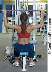 Lat Pulldown - A female fitness instructor demonstrates a...