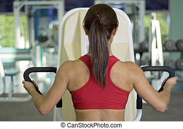 In The Gym - A woman works out on a machine in a gym