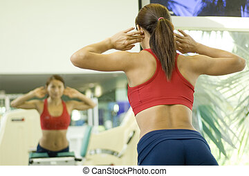 Back Raises - A woman works out at a gym looking at her...
