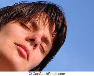 Dreaming girl - Close-up of a girl face over natural blue...