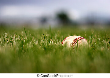 game over - a used baseball lies buried in the grass after...