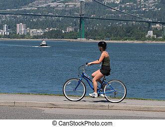 Out for a ride - Young girl riding bike on the sea wall