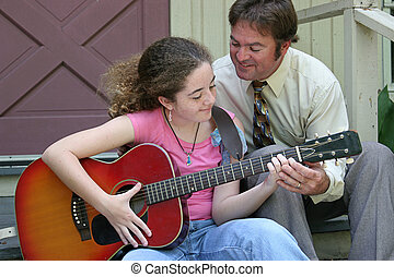 Family Guitar Lesson - A father teaching his daughter to...