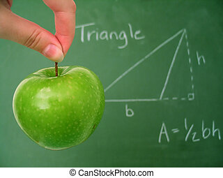 Classroom chalkboard with math, apple in focus.