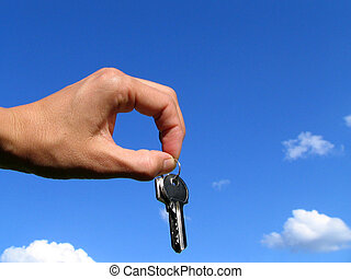 Keys in a hand on a background of the sky