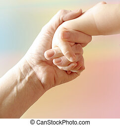 Mother child hand - Mother holding child\'s hand on pastel...